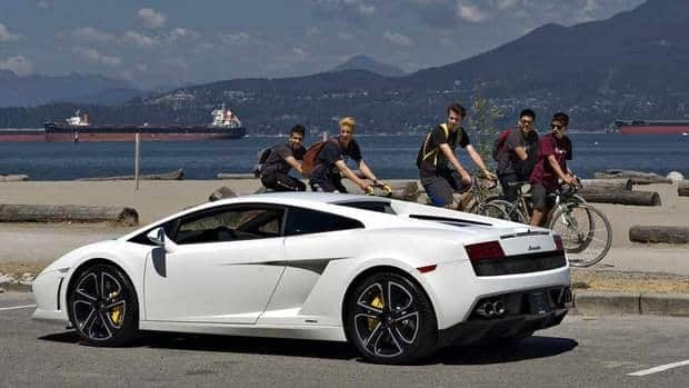 The gap between those who can afford luxuries like this Lamborghini sports car being ogled by some Vancouver cyclists, above, and those who can't even come close to doing so is growing in Canada and the U.S. In Canada, the wealthiest one per cent earn an average of $381,300 a year, compared to a meagre $38,700 for the average Canadian.