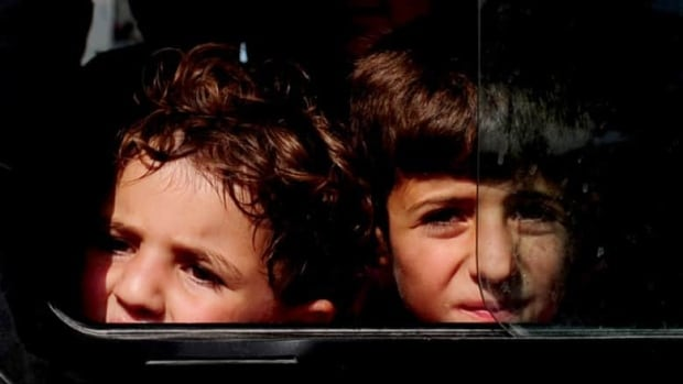 Child refugees from Syria arrive on a bus at a refugee camp in Hatay, a province in southern Turkey, on June 10.
