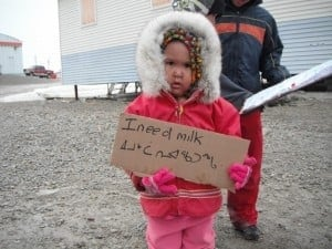 small girl holding a sign at a protest in Nunavut about unaffordable food and food insecurity in June 2002