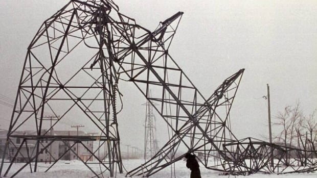 Jan. 15, 1998 -- A woman walks past a downed hydro pylon near St-Constant, Que. where hydro crews worked to reestablish power following the ice storm. (Robert Galbraith/CP)