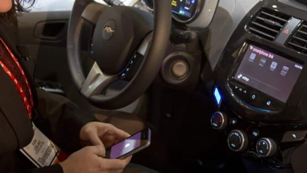 A woman links her iPhone to the MyLink system in a Chevrolet Spark. MyLink incorporates voice recognition software and can provide climate control, roadside assistance and vehicle diagnostics. (Steve Marcus/Reuters)