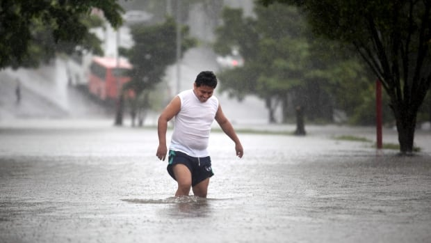 A man walks through a flooded street during heavy rains in the port city of Veracruz, Mexico on Friday. Canada has issued a Mexico travel warning for Canadians, as Ingrid strengthens to a hurricane off Mexico's Gulf Coast.