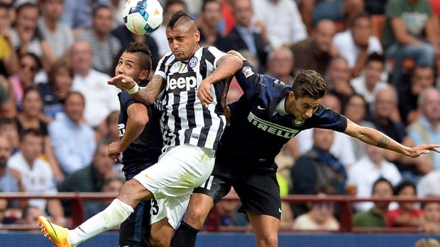 Arturo Vidal of Juventus, centre, Ricardo Alvarez, right, and Saphir Taider of FC Inter Milan compete for the ball on September 14, 2013 in Milan, Italy.