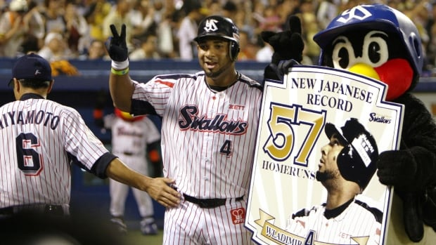 Japan's Yakult Swallows outfielder Wladimir Balentien, centre, of Curacao, Netherlands Antilles, celebrates his 57th home run as the Japanese single-season record during a baseball game against Hanshin Tigers in Tokyo on Sunday.