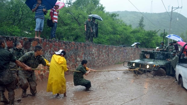 Mexican soldiers work to free a vehicle during tropical storm Manuel in the city of Chilpancingo, Mexico. Thirteen people have died amid rains from both Manuel and Hurricane Ingrid.