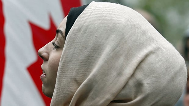 A demonstrator is framed by a Canadian flag as she protests against Quebec's proposed Charter of Values in Montreal on Sept. 14, 2013.