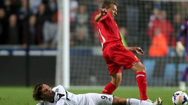 Swansea City's Miguel Michu, left, and Liverpool's Leiva Lucas compete for the ball during their match at the Liberty Stadium, Swansea Wales on Monday.