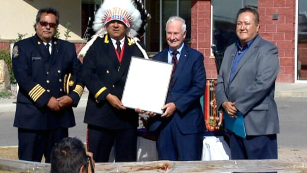 Governor General David Johnston presents Chief Fred Rabbit Carrier with a commendation award to thank all Siksika volunteers for their emergency relief efforts after the flood.