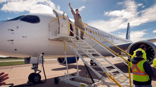 Test pilot Chuck Ellis waves to the crowd after Bombardier's CS100 maiden test flight at the Mirabel airport north of Montreal/