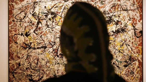A woman admires a painting by US artist Jackson Pollock. A New York art dealer has pleaded guilty to a 15-year scam that fooled collectors into buying more than $80 million US of fakes that imitate artists like Jackson Pollock and Willem de Kooning.