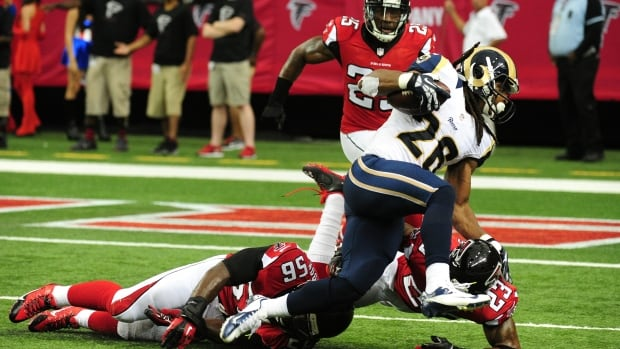 Atlanta Falcons linebacker Sean Weatherspoon, left, falls as he attemps to tackle Daryl Richardson of the St. Louis Rams, centre,  at the Georgia Dome on Sunday in Atlanta. Weatherspoon later left the game and did not return due to a foot injury and will miss at least eight weeks.