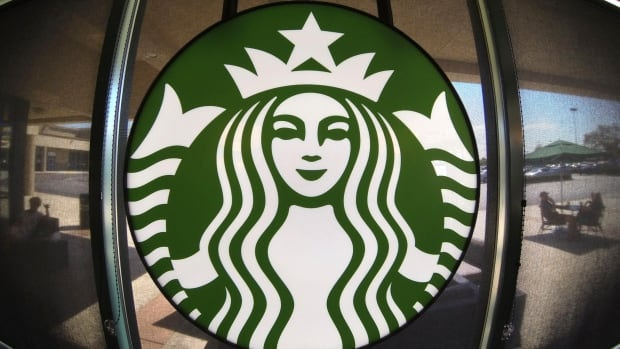 The Starbucks logo hangs on a window inside a newly designed Starbucks coffee shop in Fountain Valley, Calif.  The company is struggling with its liberal-leaning corporate image and the presence of guns in its communities.
