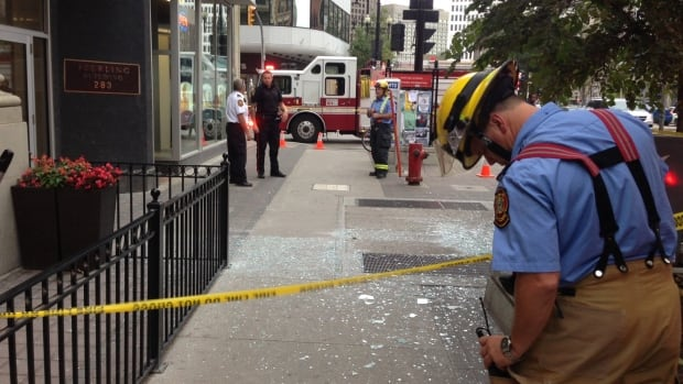 Winnipeg emergency crews cordon off broken glass on a section of sidewalk outside 283 Portage Ave. on Wednesday afternoon. Police say they received reports of an explosion there.