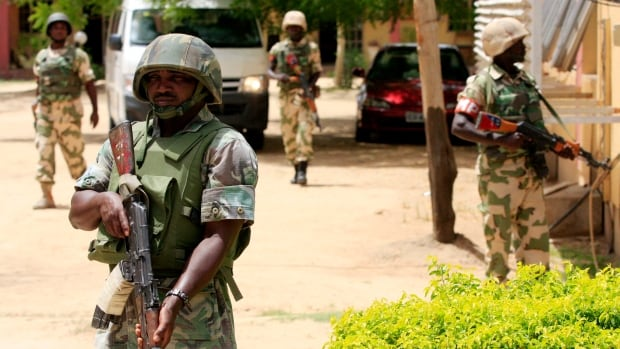 Nigerian soldiers stand guard at the offices of the state-run Nigerian Television Authority in Maiduguri, Nigeria. An environmental department official said Friday that workers combing bushes have recovered the bodies of at least 143 civilians killed by suspected Islamic militants in a Tuesday night attack.