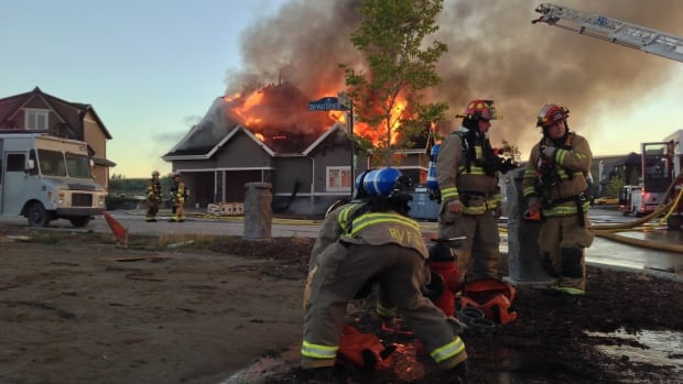 Crews battle a large house fire on the northwestern edge of Calgary early Friday.