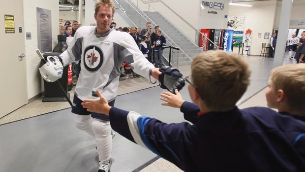 Winnipeg Jets' Ian White reaches out to a young fan on Sept. 12 in Winnipeg. On Sept. 20, White was cut from the team.