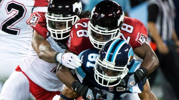 Toronto Argonauts wide receiver Jason Barnes, centre, gets tackled by Calgary Stampeders defensive backs Jonathan Hefney, left, and Brandon Smith, right, during a game last month.