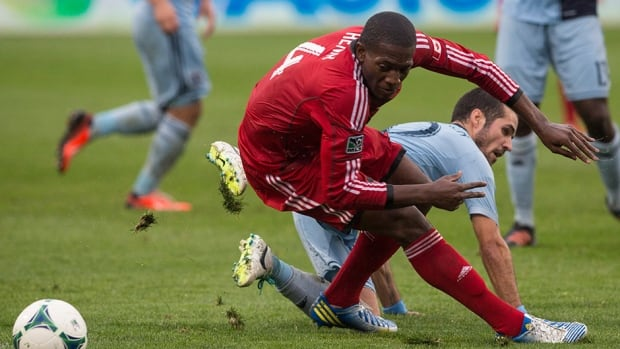 Toronto FC's Doniel Henry, left, and Sporting Kansas City's Benny Felhaber battle for the ball in Toronto on Saturday September 21, 2013.