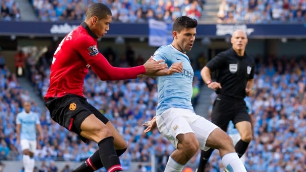 Manchester City's Sergio Aguero, centre, keeps the ball from Manchester United's Chris Smalling during their match at the Etihad Stadium in Manchester, England on Sunday.