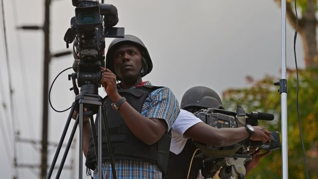 """Kenyan media wearing bulletproof jackets and helmets film near the Westgate mall in Nairobi. Security forces launched a """"major"""" assault on the mall Sept. 22 after militants held an unknown number of hostages, trying to end a two-day standoff that had already killed at least 68 people."""