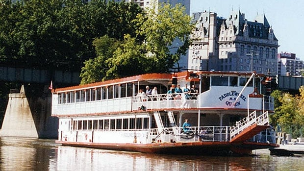 The M.S. Paddlewheel Queen passes by The Forks harbour with the historic Fort Garry Hotel seen in the background.