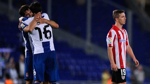 Iker Muniain, right, of Athletic Club leaves the pitch dejected after being defeated as Victor Sanchez of Espanyol and his teammate Javi Lopez celebrate their victory.