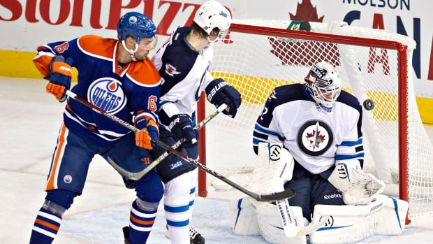 Winnipeg Jets goalie Edward Pasquale makes the save as Jacob Trouba and Edmonton Oilers Jesse Joensuu battle in front during second period NHL pre-season hockey action in Edmonton, Alta., on Monday