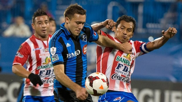 Montreal Impact's Andrew Wenger, left, and CD Heredia's Henry Medina battle for the ball during the first half in Montreal on Tuesday.