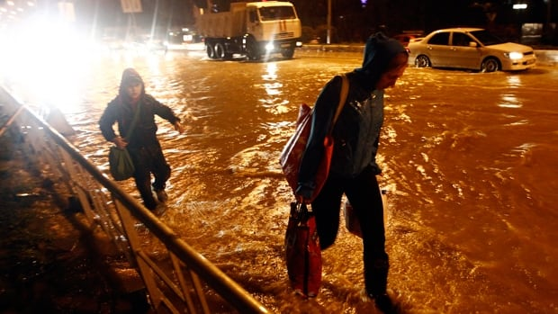 A woman and a young boy walk on a flooded street in Sochi, Russia, where a state of emergency was declared Wednesday.