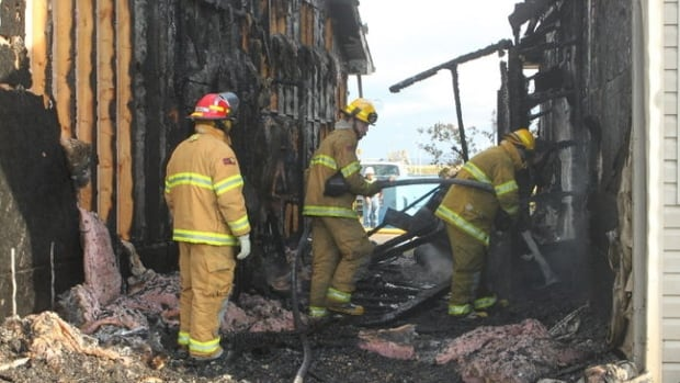 Firefighters sift through a $1-million condo fire at the Sandstone Estates in Stony Plain. A 16-year-old has been charged with arson.