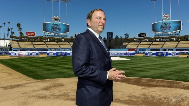 NHL Commissioner Gary Bettman walks to home plate at Dodger Stadium, after a news conference Thursday in Los Angeles.