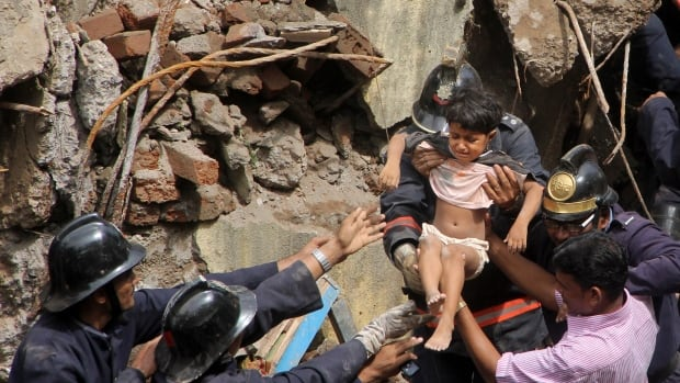 Indian Fire officials rescue a girl from debris of a collapsed building in Mumbai on Friday. The multi-storey residential building collapsed in India's financial capital of Mumbai early Friday, killing at least three people and sending rescuers racing to reach dozens of people feared trapped in the rubble.