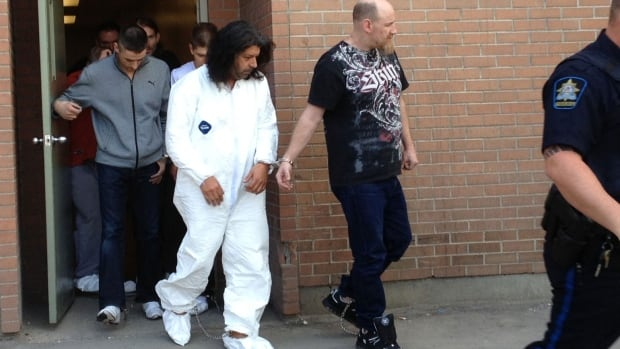 Mario Antonacci, also known as Andreas Pirelli (in white), is taken out of the Calgary Police Service arrest processing unit on Friday. The self-described Freeman-on-the-Land will be sent to Montreal where he faces outstanding charges.