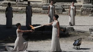Actress Ino Menegaki, right, as high priestess, holds the torch with the Olympic Flame inside the temple of Hera, after it was lit from the sun's rays during the final dress rehearsal for lighting of the Olympic flame at Ancient Olympia on Saturday.
