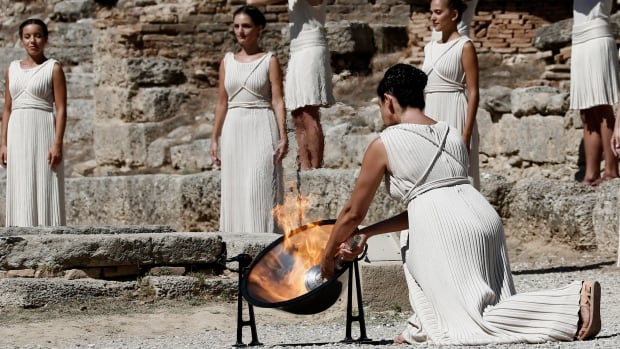 Greek actress Ino Menegaki lights a torch from the sun's rays reflected in a parabolic mirror during the torch lighting ceremony.