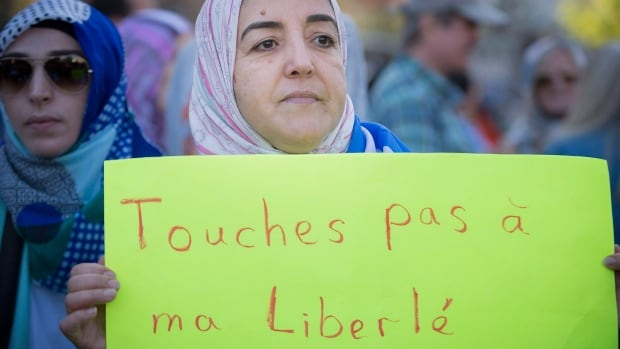 A protester holds a sign asking that no one touch her freedoms during a protest on Sunday in Montreal against the proposed charter of values by the Parti Quebecois.