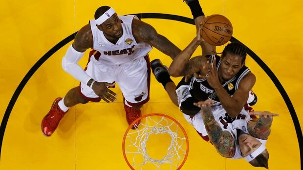 San Antonio Spurs' Kawhi Leonard, centre, drives to the basket as Miami Heat forwards Chris Andersen, right, and LeBron James defend during the NBA Finals on June 21, 2013, in Miami.