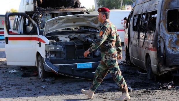 A twin suicide car bombing and ensuing firefight in the capital of Iraq's largely peaceful self-ruled northern Kurdish region killed and wounded dozens of security forces on Sunday, officials said.