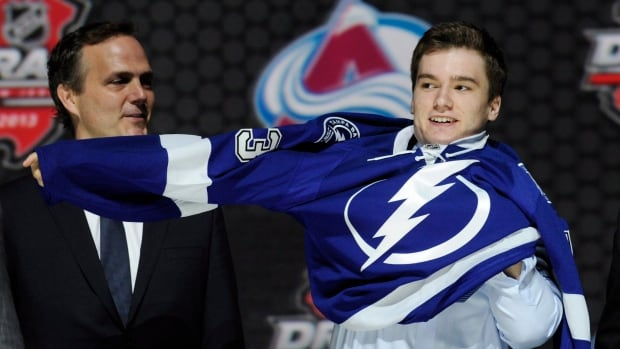 Jonathan Drouin pulls on a Tampa Bay Lightning sweater after being chosen third overall in the first round of the NHL hockey draft, Sunday, June 30, 2013, in Newark, N.J.