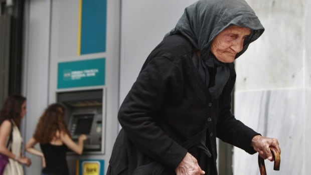 A woman makes her way by as people make a transaction at an ATM machine outside a bank in central Athens. Countries are not working quickly enough to cope with a population greying faster than ever before, a new study says.
