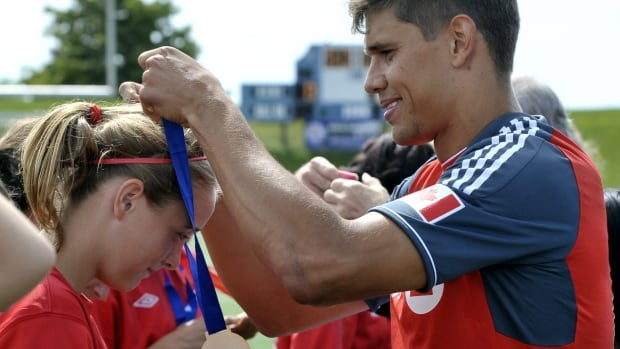 Toronto FC's Adrian Cann congratulates gold medal winners, the Brampton Brams United Bandits, at the Ontario Summer Games soccer match in Toronto, Aug. 19.  MARKETWIRE PHOTO/BMO Financial Group/BMO Bank of Montreal