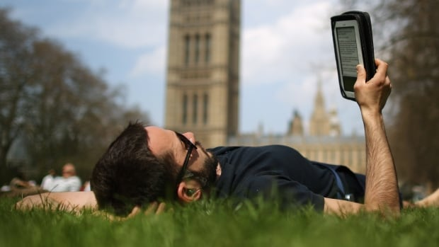 A man reads an e-book in in London in April. Online document-sharing firm Scribd and HarperCollins are teaming up for a new e-book subscription service inspired by the success of video-sharing service Netflix.