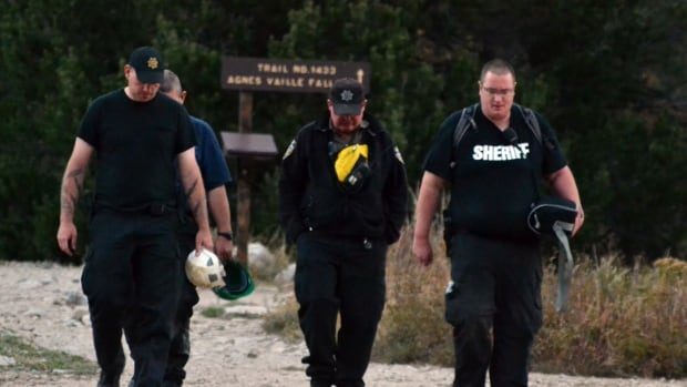 Sheriff's deputies walk out of a Colorado trail shortly after leaving the scene of a rock slide that killed five people Monday.
