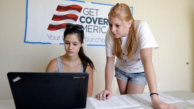 Ashley Hentze, left, of Lakeland, Fla., gets help on Tuesday signing up for health care from Kristen Nash, a volunteer with Enroll America, a private, non-profit organization running a grassroots campaign to encourage people to sign up for health care,