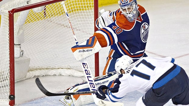 Winnipeg Jets' James Wright hits the post as Edmonton Oilers goalie Devan Dubnyk looks on during second period of their NHL game in Edmonton on Oct. 1.