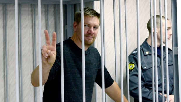 Greenpeace activist Anthony Perrett from Britain appears at a district court in Murmansk on Sept. 29. He is one of 14 people now facing charges of piracy after protesting at a Russian oil platform, according to Greenpeace.