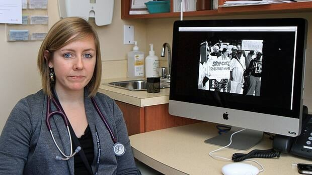 McMaster medical student Erica Roebellen is a member of Hamiltonians for Migrant and Refugee Health, which opposes the recent changes to the Federal Interim Health Program. On the monitor is a photo from Storytelling through Photographs, an exhibition that depicts healthcare professionals' response to the legislation. The series will show at Christ Church Cathedral during the James St. North Art Crawl on Friday. (Cory Ruf/CBC)