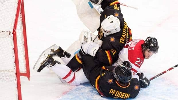 Canada forward Phillip Danault, centre, crashes into Germany goalie Elamr Trautmann, top, and Germany forward Leonhard Pfoderl, bottom, during first period IIHF World Junior Championships hockey action in Ufa, Russia. Canada won its opener easily.