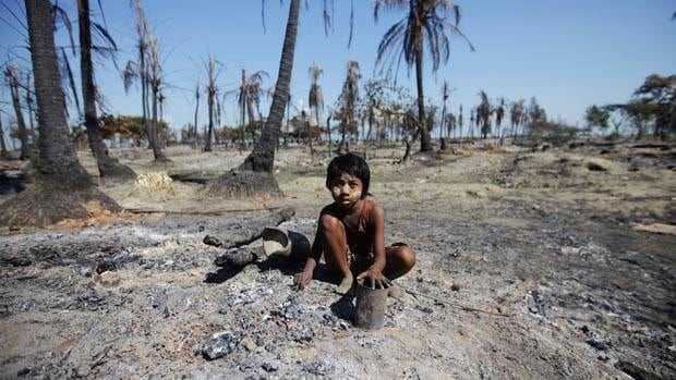 A girl collects pieces of metal from the ashes in Pauktaw township in western Burma. Boatloads of Muslims from the area sought safety on islands and in coastal villages on Saturday after a week of sectarian unrest.