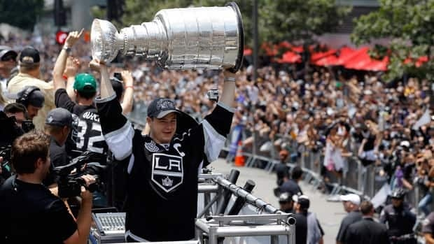 Los Angeles Kings' Dustin Brown hoists Lord Stanley's Mug over his head during the team's Stanley Cup parade on Thursday.